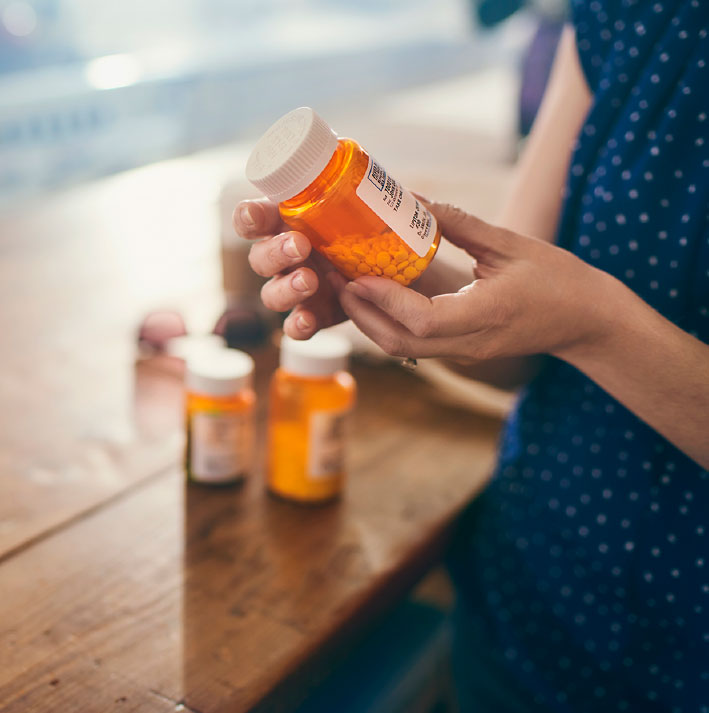 A woman looks at one of her medicine bottles