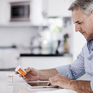 Older man holding medication bottle.