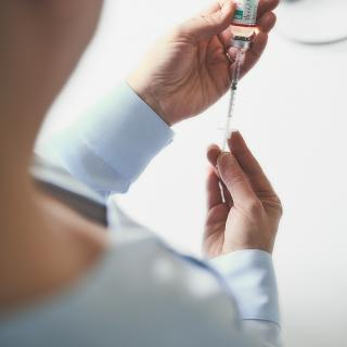 Woman holding injectable medication and needle