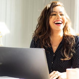Woman smiling and using a computer